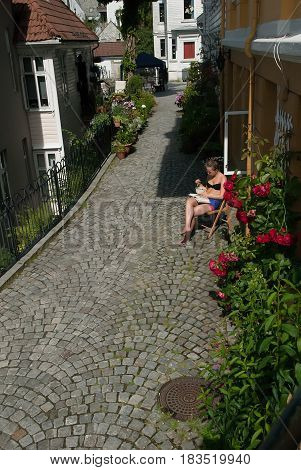 Bergen Norway - July 20 2014: girl enjoying the sunshine. Bergen is also known as the rain capital of Europe with approximately 220 days of rain in a year so sunny days like this are very rare.