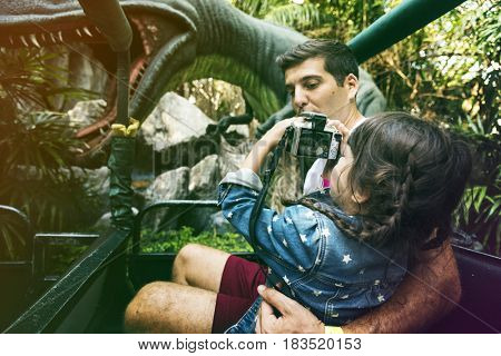 Father Hold Daughter Camera Snap Dinosaur