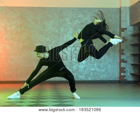 Couple of young hip-hop dancers in studio