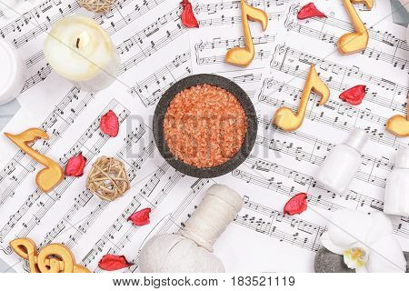 Beautiful composition of spa accessories on musical notes background