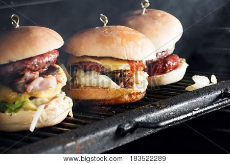 Delicious burgers with beef, tomato, cheese and lettuce. cooked on the grill assembled. heat the grill and the smoke from the fire