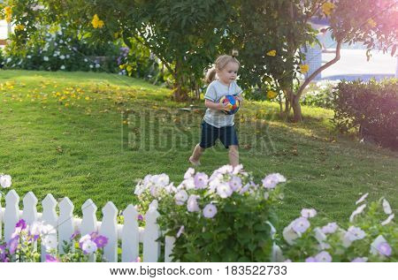 sport game and running. cute baby boy happy small little child with long blond hair holds colorful ball on green grass in garden with blossoming flowers on sunny summer day on natural background