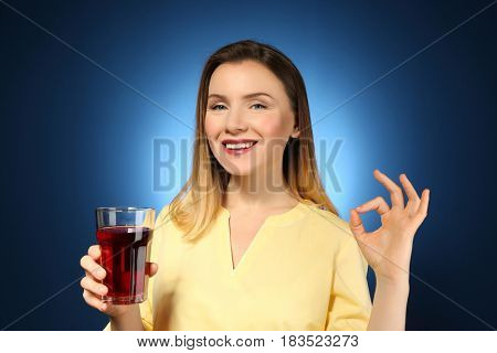 Beautiful woman with glass of fresh juice on color background