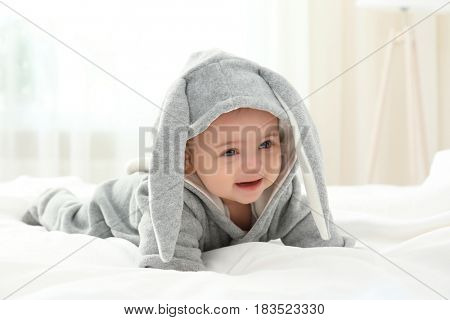 Cute little baby in bunny costume lying on bed at home