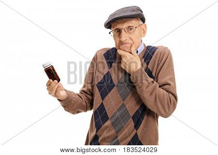 Confused senior holding a bottle of pills isolated on white background