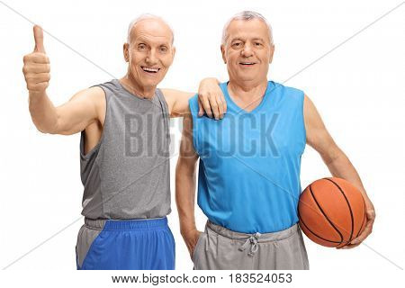 Happy seniors in sportswear with a basketball making a thumb up gesture isolated on white background