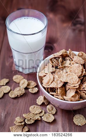 Flakes of cereals with a glass of milk on a wooden table. Oat flakes in a deep bowl in a rustic style. Simple coarse flakes with milk.