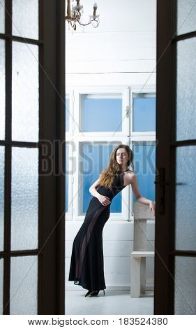 Pretty girl or beautiful fashion woman with long blond hair in black dress holding brown cup seen through open doors on window background