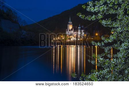 Lillafured palace at evening time. Illuminated building reflects in lake. Blossom tree in foreground.