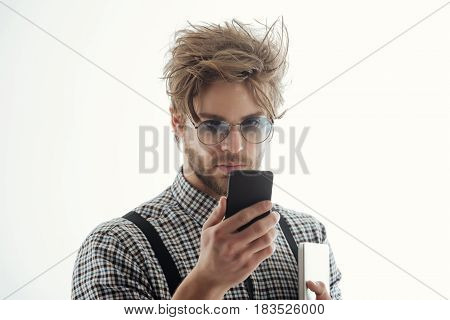 Handsome man or male student businessman with beard and stylish blond hair in nerd glasses with smartphone and laptop computer. Using technology internet surfing and video conferencing
