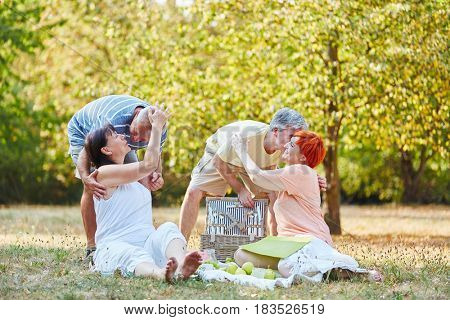 Happy senior couples making a picnic in summer at the park