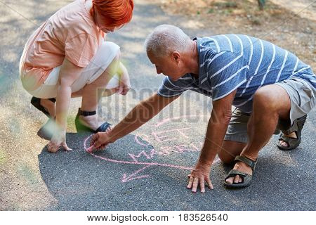 Senior couple drawing a heart with the text
