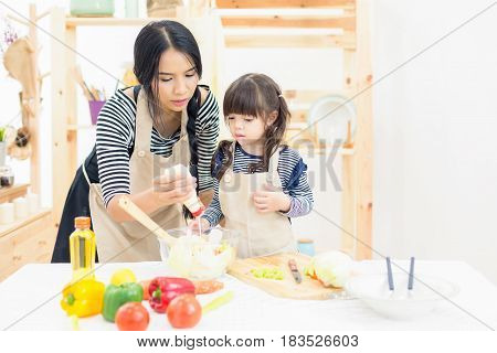 A little girl learning cooking practice with her Mom on salad bowl in kitchen background