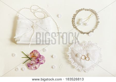 Wedding background. Bride accessories: rings handbag boutonniere necklace. Top view.