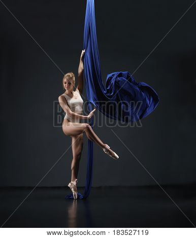 Pretty blonde in beige bodysuit and pointeshoes exercising on nice blue aerial silks