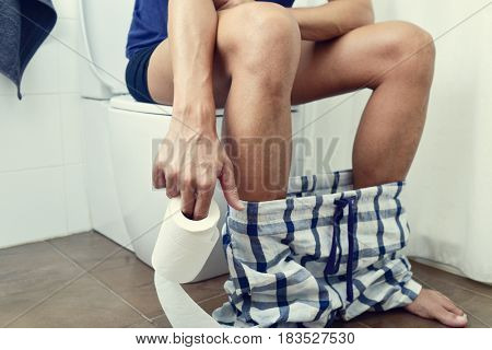 detail of a young caucasian man in the toilet sitting in the bowl, with a roll of toilet paper in his hand