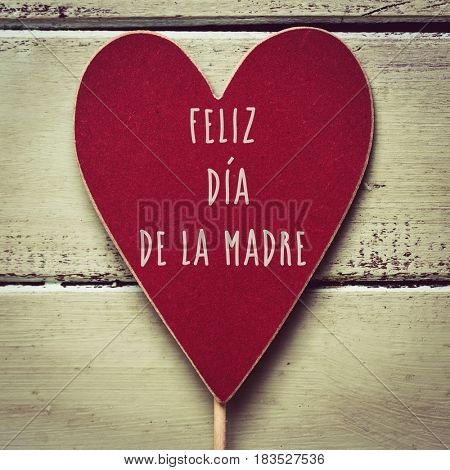 closeup of a red heart-shaped signboard with the text feliz dia de la madre, happy mothers day written in spanish, against a pale green rustic wooden background