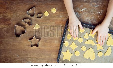Top View Of Child With Raw Shaped Cookies On Baking Tray And Cookie Cutters On Wooden Table