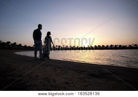 Romantic couple of pretty girl woman and handsome man walking on tropical sandy beach along sea or ocean water in evening dusk on grey sky background. Idyllic summer vacation. Love and romance