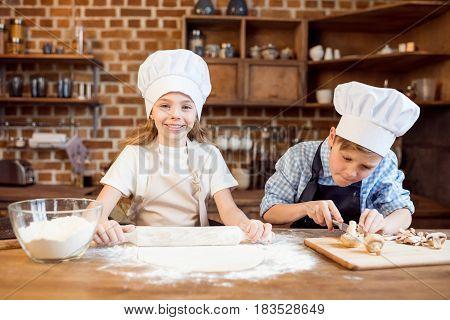 Children Making Pizza Dough And Preparing Pizza Ingredients In Kitchen