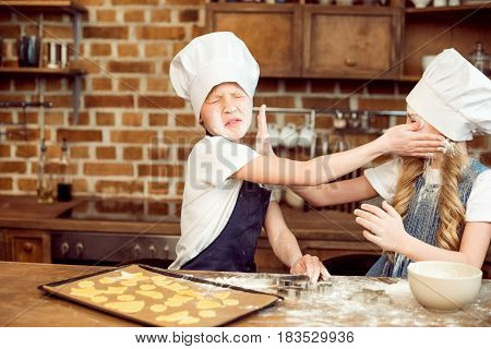 Little Boy And Girl Playing With Flour While Making Shaped Cookies