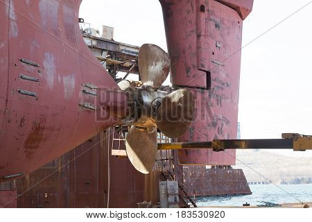 Slavynka Russia - April 21th 2017: Port Slavynka ship-repair factory sea ship-repair dock with a vessel in it the screw of a vessel and a wheel feather.
