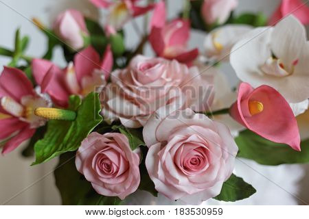 Flowers made from pastry mastic, cake with decorative white, green and pink elements, sugar flowers concept