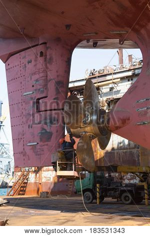 Slavynka Russia - April 21th 2017: Port Slavynka ship-repair factory sea ship-repair dock with a vessel in it the person repairs the vessel screw.