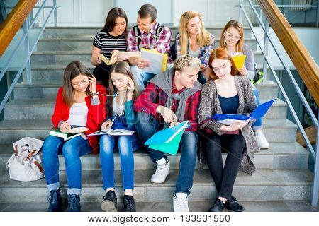 Group of university students sitting on stairs