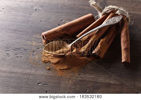 Cinnamon Sticks And Powder On A Wooden Table