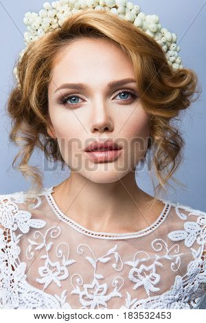 Glamour portrait of beautiful girl model with makeup and romantic wavy hairstyle. Fashion shiny highlighter on skin, sexy gloss lips make-up and dark eyebrows.