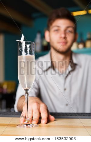 Barman offers champagne glass in night club. Professional male bartender at work in bar made an alcohol drink for party. Focused on glass