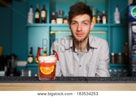 Barman offers frothy exotic spicy alcohol cocktail with chili peppers and orange in restaurant at bar background. Glass on bar table, original and creative refreshing drink. Selective focus on glass