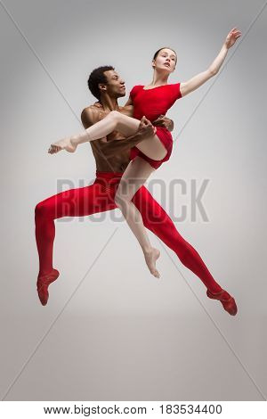 Couple of ballet dancers dancing over gray background