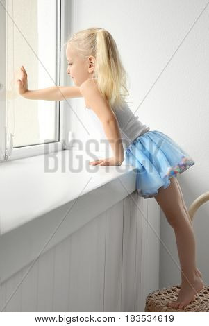 Cute little girl standing on chair near window