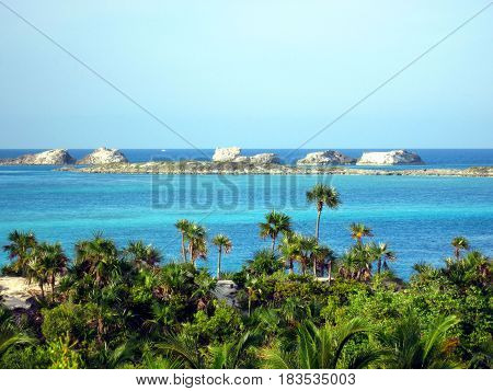Palm tree fringed island with turquoise crystal clear water