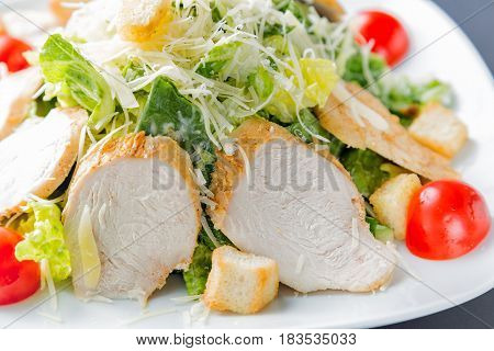 Healthy green organic caesar salad close up on white plate.