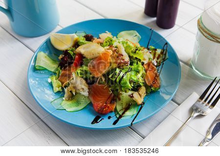 Restaurant healthy food, seafood salad closeup. Salmon and cod fish salad with vegetables and lettuce on blue plate. Appetizing dish served with sauce, dinner meal. Selective focus