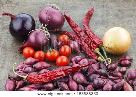 colorful display of onions,tomatoes and dried chili peppers  on a metal tray background