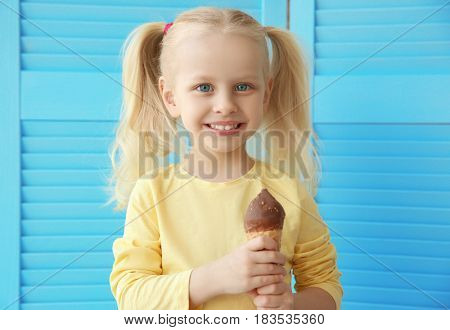 Cute little girl eating ice cream on folding screen background