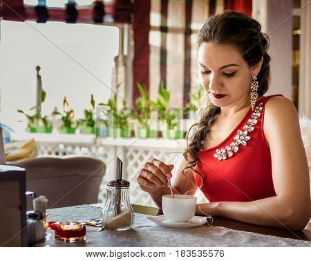 Young gGirl with scythe in a red dress with a brooch drinking tea in a cafeirl with scythe in a cafe