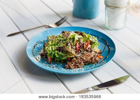 Restaurant food on white wood. Warm meat salad with sesame, vegetables and lettuce on blue plate. Appetizing dish served with soy sauce, dinner meal.