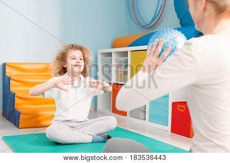 Child Playing Ball With Physiotherapist