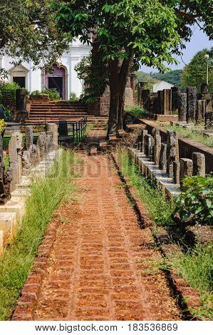 Archaeological Museum artifacts under the open sky is located near the Church of St. Francis de Assisi in Old Goa, India. Brick walkway to the Church.