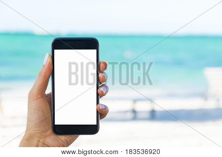 Beautiful woman's hand using smart phone at beach. Smartphone white screen.Blank empty screen