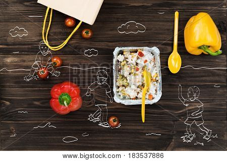 Summer freshness, Top view of bellpeppers lying on the wooden table near foil bowl with cooked rice