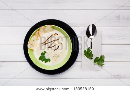 French cuisine restaurant food top view. Creamy mushroom soup with croutons in green bowl on white wood background.