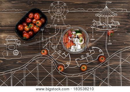 So delicious. Top view of cherry tomatoes on the wooden table while bowl with greek salad standing nearby