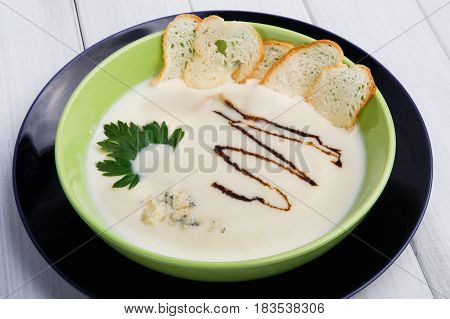 Healthy meal, creamy mushroom soup with croutons in green bowl on white wood background. French cuisine restaurant food closeup. Hot dish.