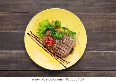 Beef steak with vegetables and parsley, top view. Appetizing meat dish served with sauce, dinner meal.